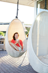 Finland, Uusimaa, Helsinki, Kaivopuisto, Smiling young woman using smart phone in swing chairの写真素材 [FYI02703984]