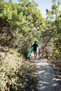 Australia, Queensland, Sunshine Coast, Noosa, Alexandria Bay, Young man carrying surfboardの写真素材 [FYI02703997]