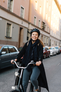 Sweden, Sodermanland, Stockholm, Sodermalm, Heleneborgsgatan, Young woman cycling on streetの写真素材 [FYI02704001]
