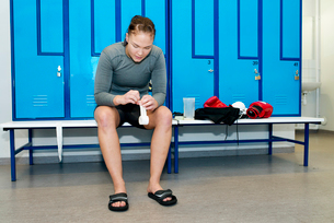 Sweden, Female boxer sitting on bench in locker roomの写真素材 [FYI02704018]