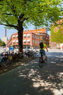 Sweden, Stockholm, Man on bicycle in front of Royal Institute of Technologyの写真素材 [FYI02704020]
