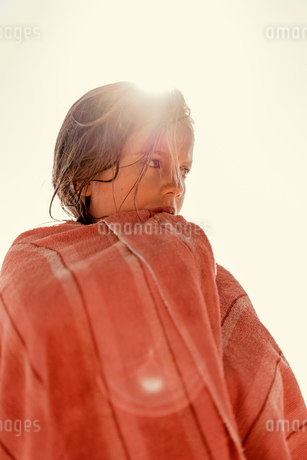 Sweden, Smaland, Tjust archipelago, Vastervik, Hasselo, Girl (8-9) wrapped in towel against skyの写真素材 [FYI02704027]