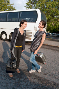 Sweden, Ostergotland, Norrkoping, Two sisters talking in front of busの写真素材 [FYI02704050]