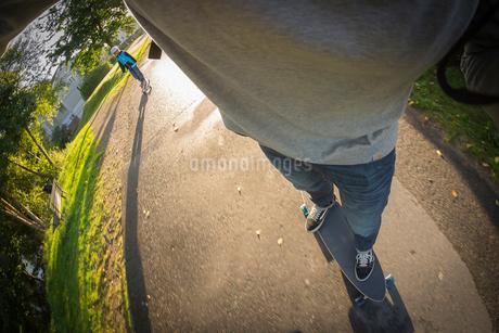 Sweden, Vastergotland, Lerum, Low-section shot of skater riding shortboard followed by boy (10-11)の写真素材 [FYI02704054]