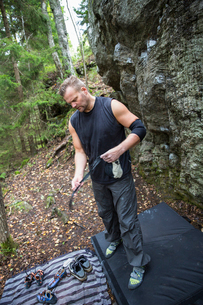 Sweden, Sodermanland, Tyreso, Sportsman with rock climbing equipment in forestの写真素材 [FYI02704069]