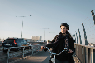 Sweden, Sodermanland, Stockholm, Vasterbron, Young woman walking with bikeの写真素材 [FYI02704077]