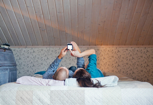 Finland, Couple lying on bed and using smart phoneの写真素材 [FYI02704093]