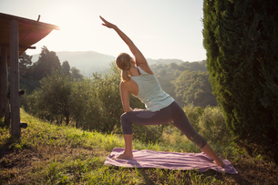 Italy, Tuscany, Dicomano, Woman practicing yoga against green hillsの写真素材 [FYI02704103]