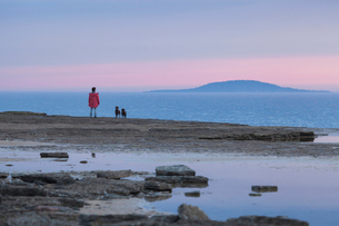 Sweden, Oland, Woman with dog standing on shoreの写真素材 [FYI02704120]