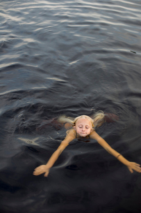 Sweden, Smaland, Braarpasjon, Girl (10-11) swimming in lakeの写真素材 [FYI02704135]
