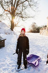 Sweden, Blekinge, Solvesborg, Portrait of girl (12-13) with plastic sledの写真素材 [FYI02704136]