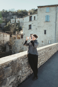 France, Languedoc-Roussillon, Sauve, Young woman photographing with smart phoneの写真素材 [FYI02704156]