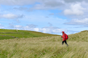UK, Scotland, Shetland, Yell, Otterswick, Senior woman hiking in grasslandの写真素材 [FYI02704168]