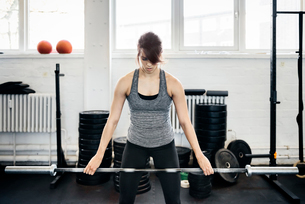 Germany, Young woman training with barbell in gymの写真素材 [FYI02704172]