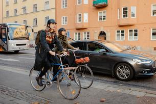 Sweden, Uppland, Stockholm, Vasatan, Sankt Eriksgatan, Man and woman cycling on city streetの写真素材 [FYI02704182]