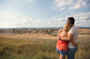 Italy, Tuscany, Hugging couple looking at field landscapeの写真素材 [FYI02704188]