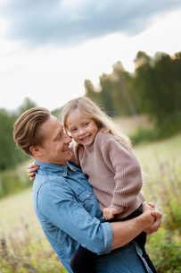 Finland, Uusimaa, Raasepori, Karjaa, Father holding in arms his daughter (6-7)の写真素材 [FYI02704190]