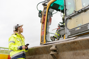 Sweden, Vastmanland, Woman talking to man inside earth mover at construction siteの写真素材 [FYI02704191]
