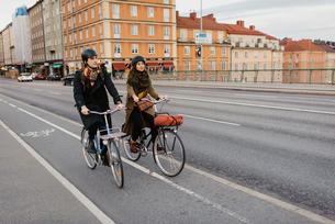 Sweden, Uppland, Stockholm, Vasatan, Sankt Eriksgatan, Man and woman cycling on city streetの写真素材 [FYI02704194]