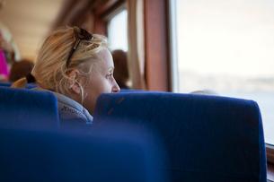 Sweden, Gothenburg Archipelago, Vastergotland, Styrso, Mature blonde woman looking through train winの写真素材 [FYI02704205]