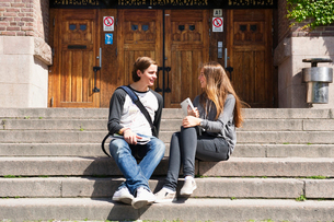 Sweden, Stockholm, Ostermalm, Students sitting on stairs in front of school buildingの写真素材 [FYI02704222]