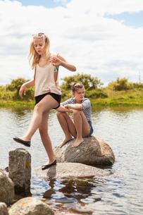 Sweden, Blekinge, Solvesbor, Torso, Teenage girls (14-15) walking and sitting on rocks in waterの写真素材 [FYI02704223]