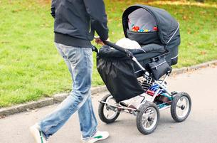 Sweden, Vastra Gotaland, Goteborg, Man pushing baby carriage in Slottskogen parkの写真素材 [FYI02704234]