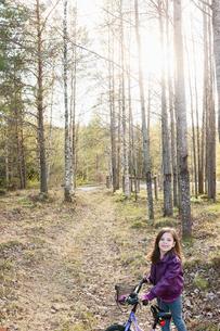 Sweden, Vastmanland, Bergslagen, Hallefors, Silvergruvan, Little girl (4-5) with bicycle in forestの写真素材 [FYI02704236]