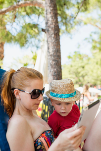 Turkey, Mugla, Marmaris, Mother and son (4-5) using tablet on summer holidayの写真素材 [FYI02704255]