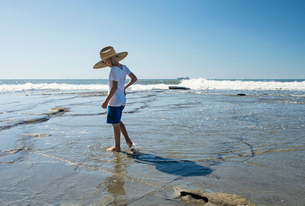 Australia, Queensland, Sunshine Coast, Moffat Beach, Boy (6-7) in straw hat standing in water on beaの写真素材 [FYI02704275]