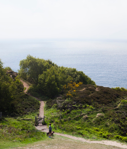 Denmark, Bornholm, Allinge, Mature woman with dogs, Baltic sea in backgroundの写真素材 [FYI02704289]