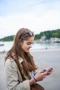 Sweden, Stockholm Archipelago, Sodermanland, Uto, Teenage girl (14-15) using smart phoneの写真素材 [FYI02704304]