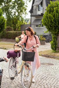 Sweden, Blekinge, Solvesborg, Women walking with bicyclesの写真素材 [FYI02704331]