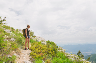France, Pelleautier, Ceuse, Woman standing on hiking path on mountain sideの写真素材 [FYI02704334]