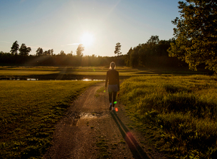 Sweden, Uppland, Orbyhus, Woman walking along footpath in meadow at sunsetの写真素材 [FYI02704358]