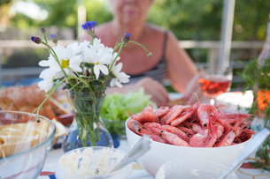 Sweden, Vastergotland, Lerum, Bowl of shrimps and flower vase on table, woman sitting in backgroundの写真素材 [FYI02704367]