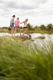 Sweden, Blekinge, Solvesbor, Torso, Teenage girls (14-15) walking on rocks in waterの写真素材 [FYI02704377]
