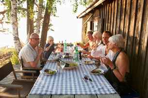 Sweden, Stockholm, Sodermanland, Dalaro, Group of people sitting at table outsideの写真素材 [FYI02704383]