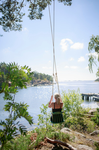 Sweden, Stockholm Archipelago, Sodermanland, Mefjard, Rear view of woman on swingの写真素材 [FYI02704384]