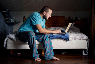 Finland, Man sitting on bed and using laptopの写真素材 [FYI02704395]