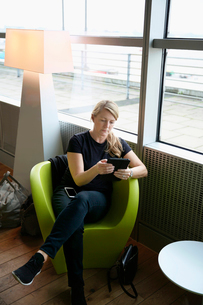 Germany, Hamburg, Mature woman sitting at airport hall and using tabletの写真素材 [FYI02704404]