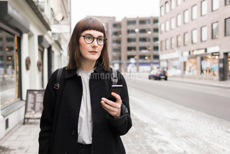 Sweden, Skane, Malmo, Young woman using mobile phone in streetの写真素材 [FYI02704405]