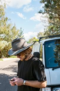 Australia, Queensland, Sunshine Coast, Noosa, Alexandria Bay, Young man using mobile phoneの写真素材 [FYI02704412]