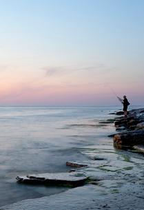 Sweden, Oland, Sandvik, Man fishing at sunsetの写真素材 [FYI02704423]