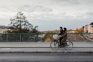 Sweden, Uppland, Stockholm, Vasatan, Sankt Eriksgatan, Man and woman cycling on city streetの写真素材 [FYI02704433]