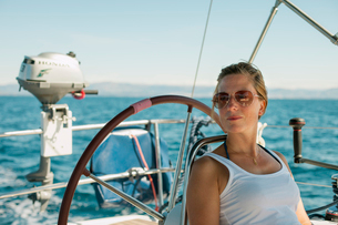 Croatia, Woman leaning against steering wheel of yachtの写真素材 [FYI02704451]