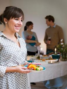 Sweden, Woman serving food, people in backgroundの写真素材 [FYI02704470]