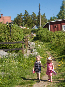 Sweden, Medelpad, Sundsvall, Girls (4-5) walking in countryside holding handsの写真素材 [FYI02704480]