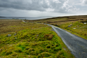 UK, Scotland, Shetland, Yell, Road in grasslandの写真素材 [FYI02704484]