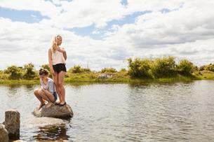 Sweden, Blekinge, Solvesbor, Torso, Teenage girls (14-15) on rock in waterの写真素材 [FYI02704498]